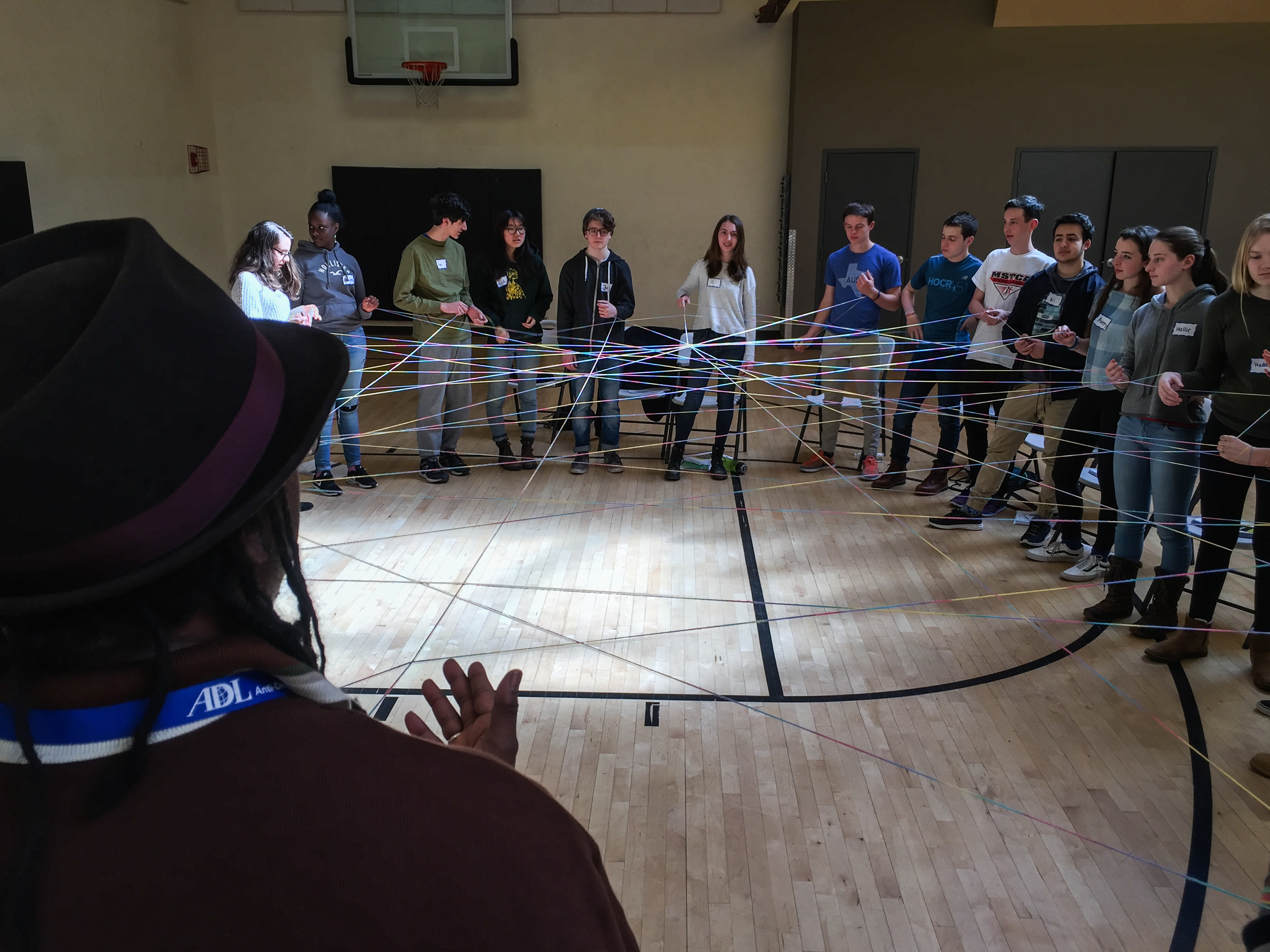 Rob Jones, a training consultant with the Anti-Defamation League, leads Brookline High School students in building a 'web of unity.'     (Tovia Smith /NPR)