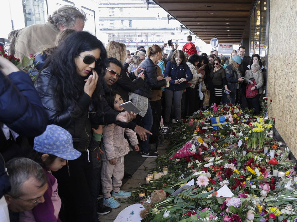 Thousands gathered Sunday at the Swedish department store where a 39-year-old Uzbek man is suspect of committing a deadly truck attack. Police say the suspect had been ordered to leave the country and expressed extremist sympathies. (Markus Schreiber/AP)