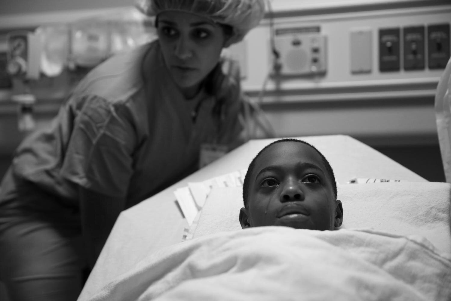 Tavon Tanner tears up before surgery at Lurie Children's Hospital on Oct. 17 to remove the bullet that ripped through his pancreas, stomach, spleen, a kidney and his left lung before becoming lodged just below his shoulder. (E. Jason Wambsgans/Chicago Tribune/Courtesy of Columbia University)
