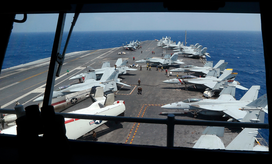 """Fighter jets onboard the U.S. Navy aircraft carrier USS Carl Vinson off the disputed South China Sea on March 3. The carrier was recently ordered to """"report on station in the Western Pacific Ocean,"""" instead of sailing for Australia as planned. (Bullit Marquez/AP)"""