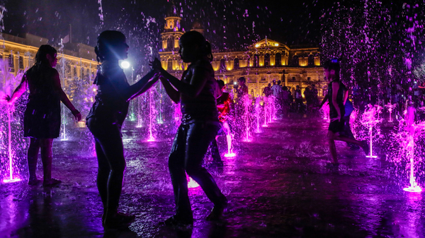 Children frolic at a plaza with a fountain in Managua.