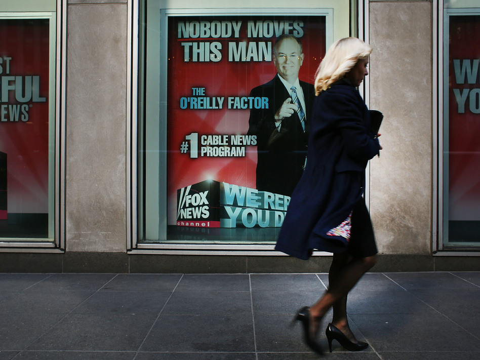 An ad for Bill O'Reilly's top-rated Fox News show stares back at passersby outside the News Corp. headquarters in New York City earlier this month. O'Reilly is stepping away from the show for a vacation as controversy continues to mount around sexual harassment claims. (Spencer Platt/Getty Images)
