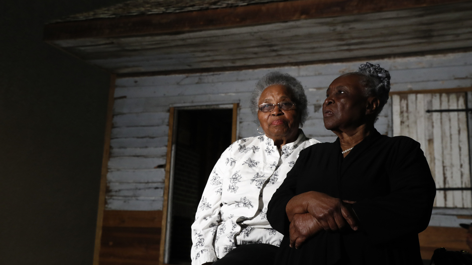 Emily Meggett (left) and Isabell Meggett Lucas sit together at the National Museum of African American History and Culture in front of a slave cabin on display that they grew up in. (Carolyn Kaster/AP)
