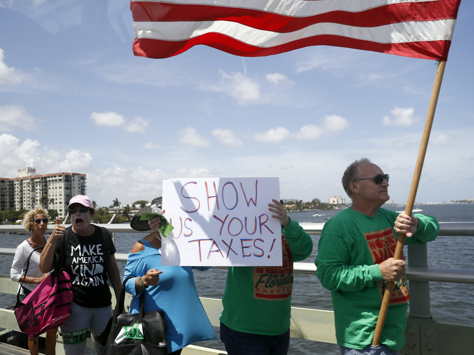 Protesters walk during a rally to encourage the release of President Donald Trump's tax returns on Saturday, April 15, 2017, in Palm Beach, Fla. (Alex Brandon/AP)