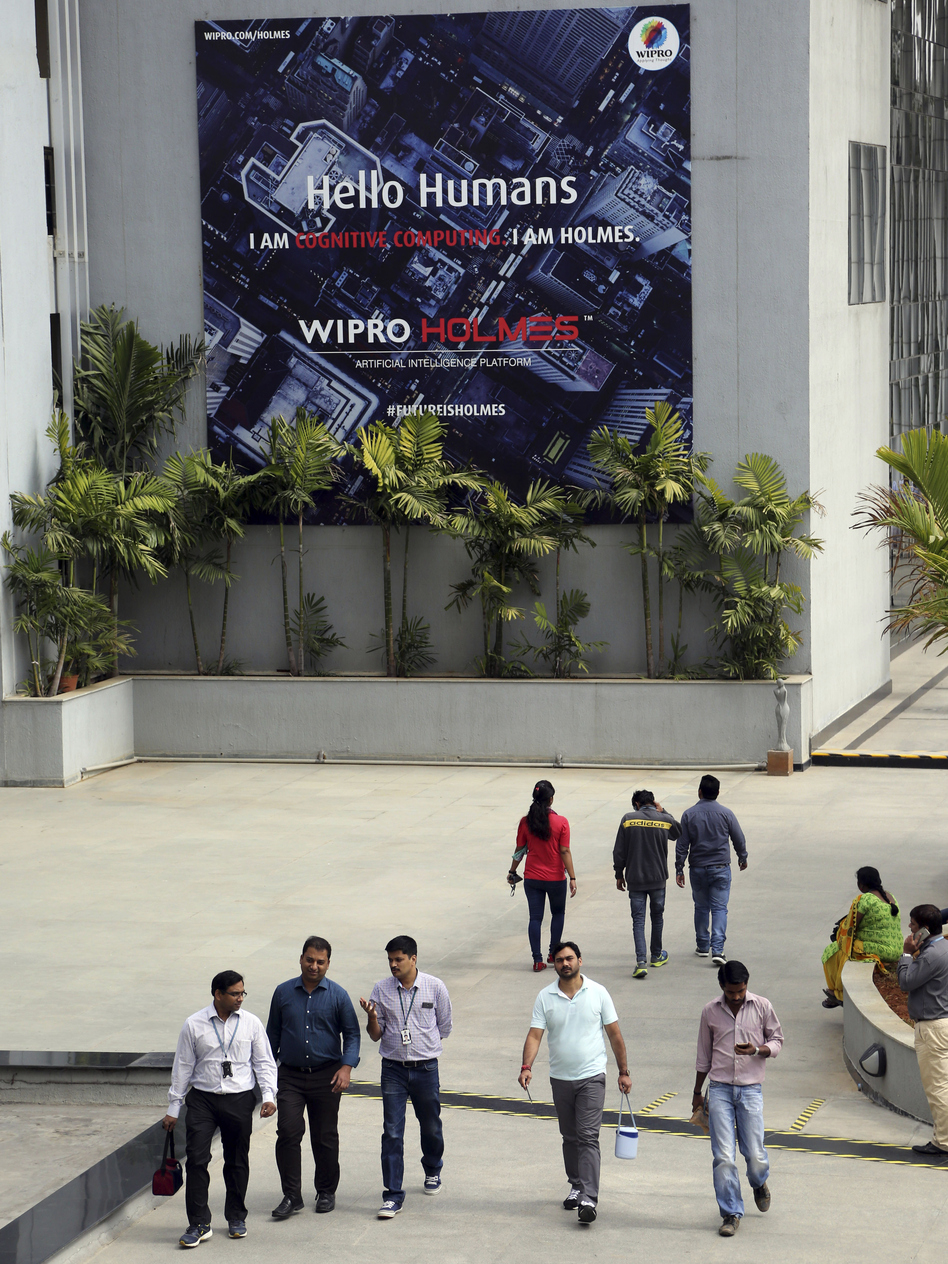 Wipro Ltd. employees walk inside the company's compound in January during a break at their headquarters in Bangalore, India. Top Indian IT companies are in the crosshairs of proposed changes to U.S. H-1B visas, including an executive order President Trump is expected to sign Tuesday. (Aijaz Rahi/AP)