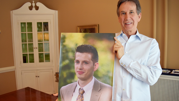 Dr. James Baker, holds a photo of his son, Max, who had been sober for more than a year and was was in college when he relapsed after surgery and died of a heroin overdose.