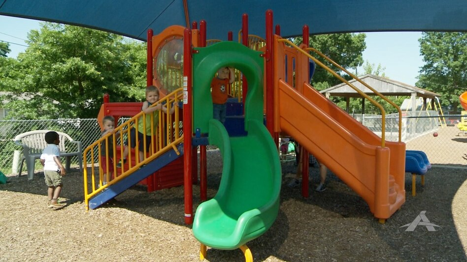 Children play on a swing set at the Trinity Lutheran Child Learning Center playground in Columbia, Mo.