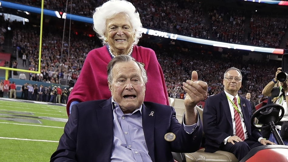 Former President George H.W. Bush tosses the coin as his wife, Barbara, watches at the start of February's Super Bowl game between the Atlanta Falcons and the New England Patriots in Houston.