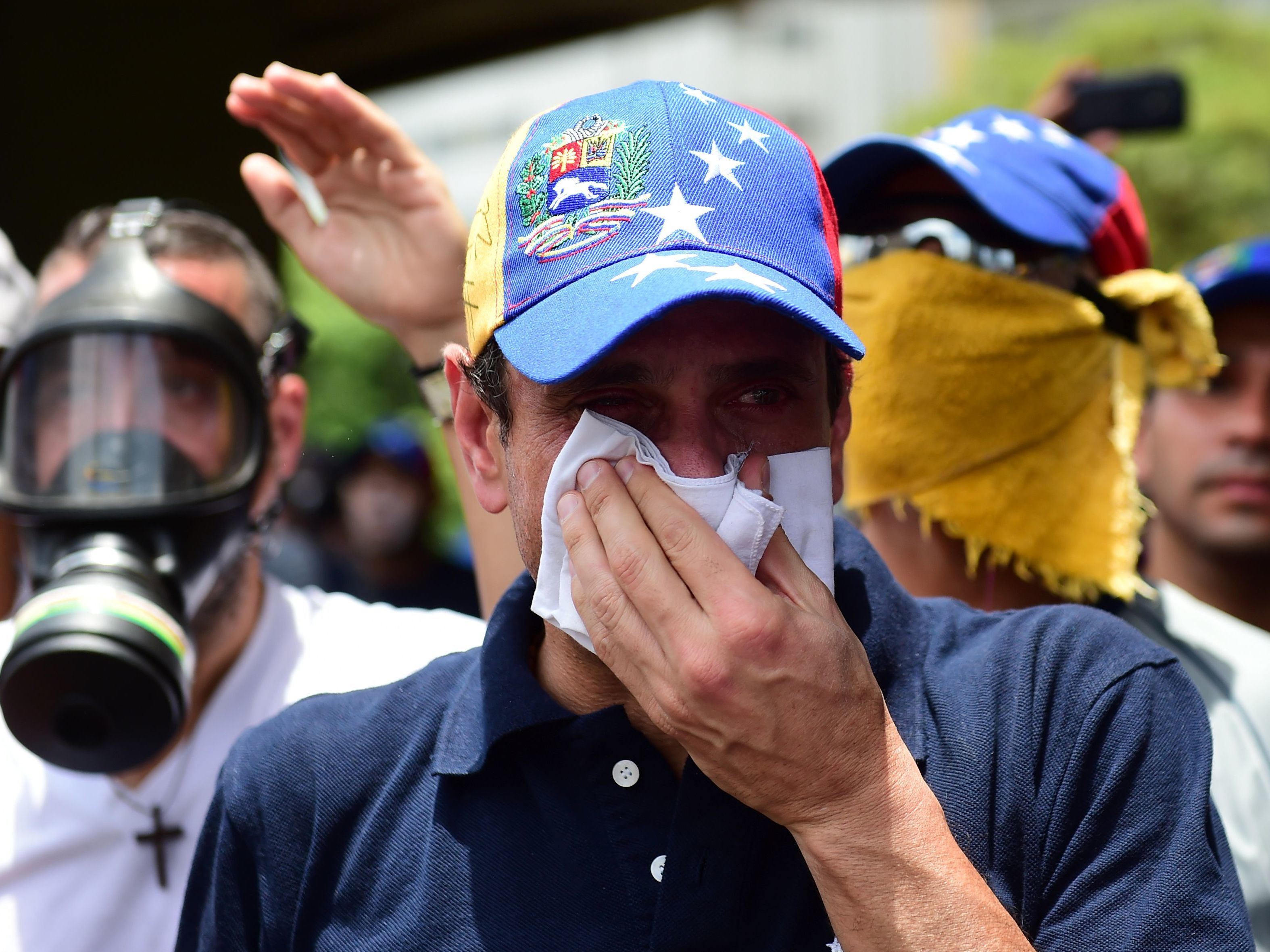 Opposition leader Henrique Capriles, who was banned from public office for 15 years, protects himself against tear gas during a rally against Venezuelan President Nicolas Maduro on Wednesday.     (Ronaldo Schemidt/AFP/Getty Images)