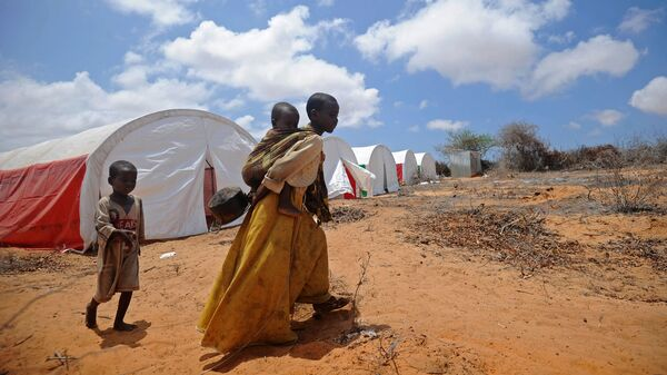 Somali children walk to a food distribution on the outskirts of Mogadishu, on April 9.