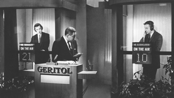 Host Jack Barry conducts questioning of contestants James Snodgrass (left) and Hank Bloomgarden (right) in supposed isolation booths during the program Twenty-One. Albert Freedman, producer of the show, died on April 11 at age 95.