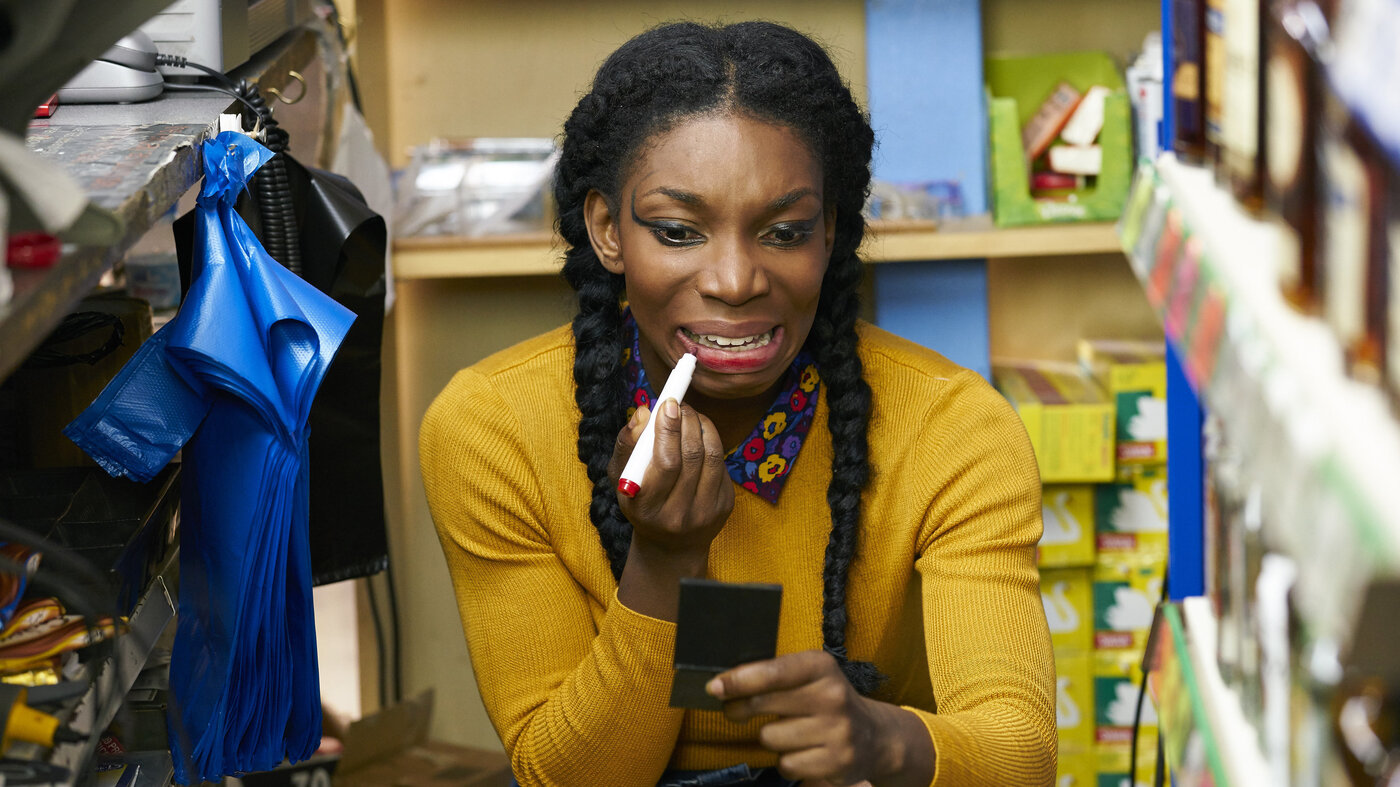 Michaela Coel as Tracey in Chewing Gum. Tracey crouches in a store room, frantically applying lipstick with what looks like a felt tip pen.