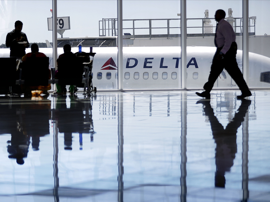 Delta recently authorized supervisors to offer up to $9,950 in compensation to passengers bumped from flights. A Delta Air Lines jet sits at a gate at Hartsfield-Jackson Atlanta International Airport. (David Goldman/AP)
