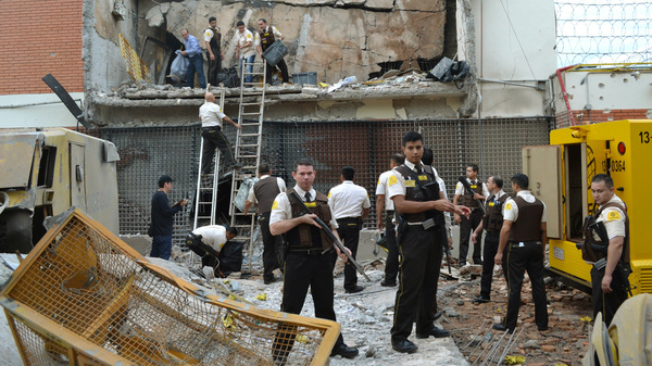Guards and police inspect a vault that the assailants blew up early morning in Ciudad del Este, Paraguay on Monday.