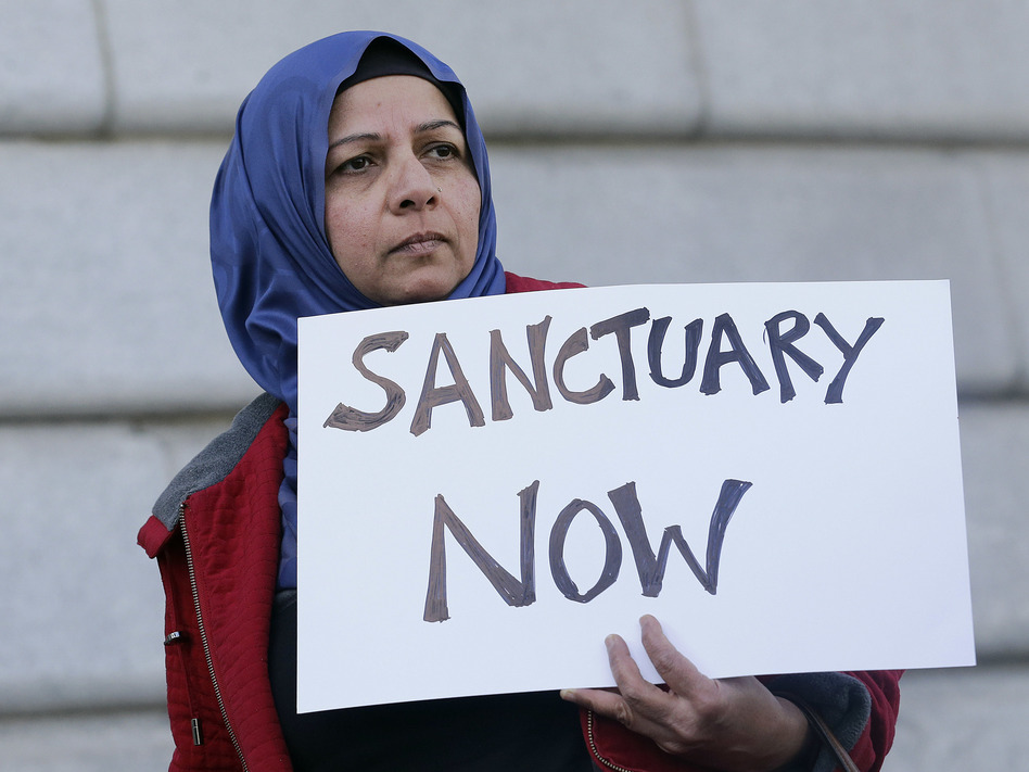 Protester Moina Shaiq holds a sign at a rally outside City Hall in San Francisco. On Tuesday, a federal judge blocked a Trump administration order to withhold funding from sanctuary communities. (Jeff Chiu/AP)