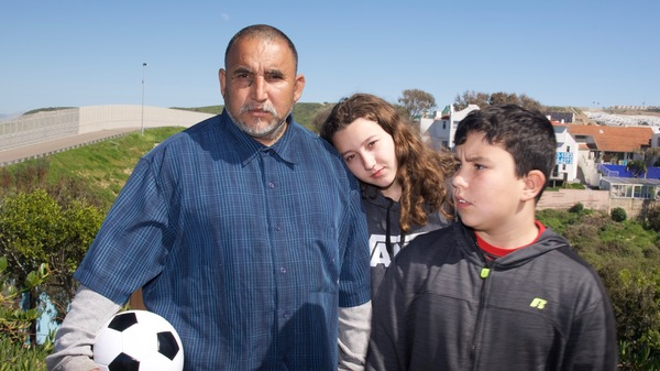 Zola Cervantes (center) and her brother, Tines, travel across the border regularly to visit their father, Gilbert, in Tijuana, Mexico.