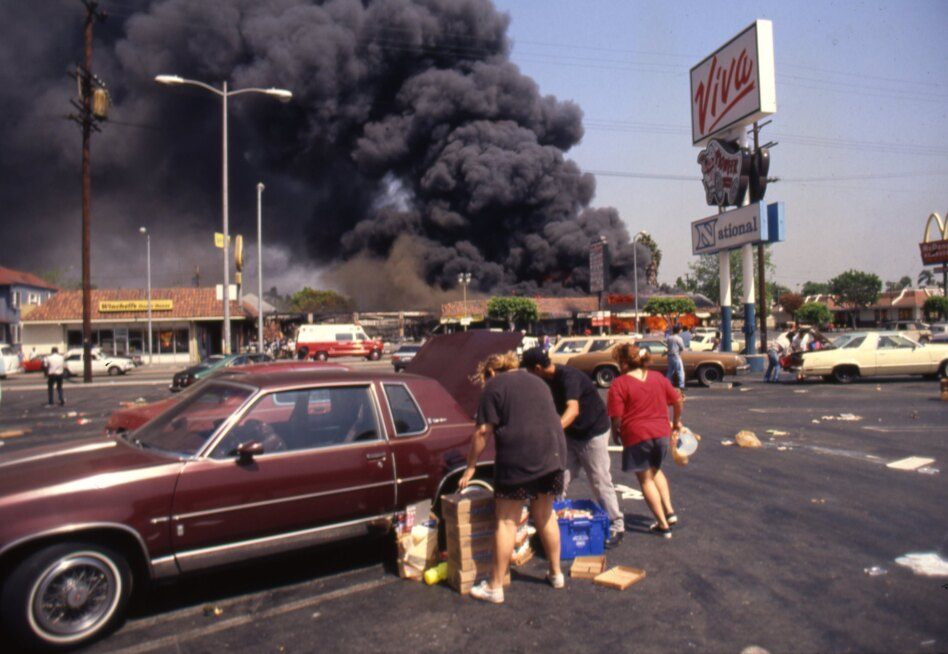 Looters load up a car at the Viva shopping center near a billowing fire during the rioting that erupted in Los Angeles on April 29, 1992, after a jury found four Los Angeles Police Department officers not guilty in the beating of Rodney King. (Ron Eisenbeg/Michael Ochs Archives/Getty Images)