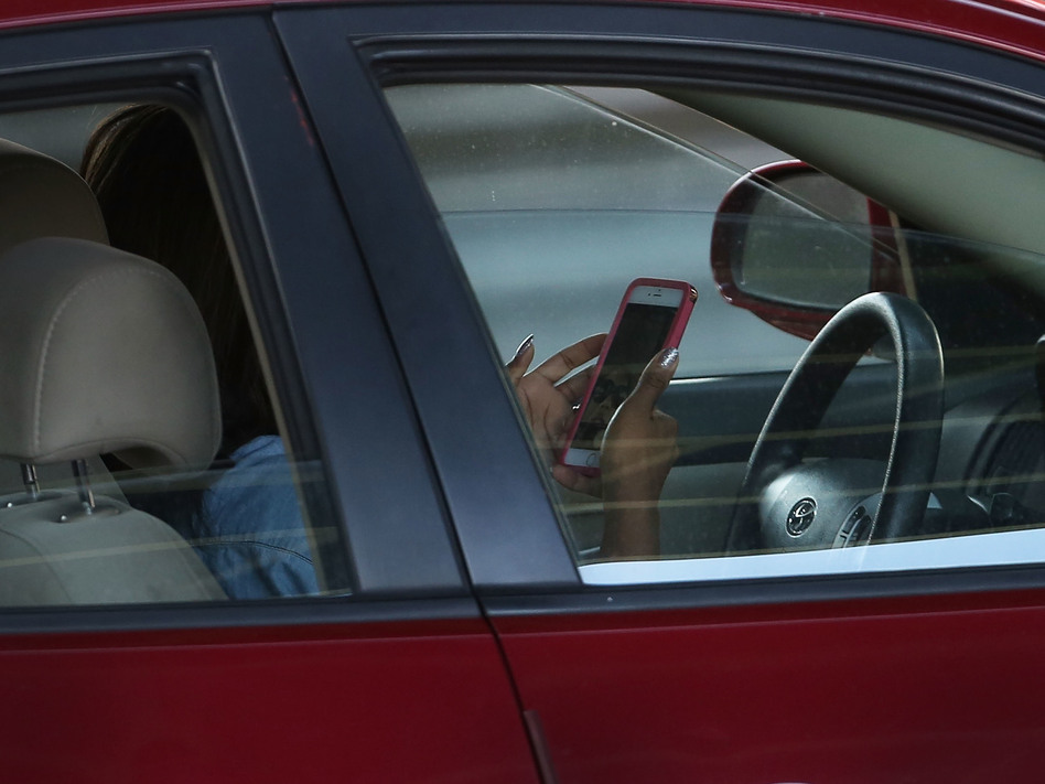 A driver uses a phone while behind the wheel of a car on April 30, 2016, in New York City. (Spencer Platt/Getty Images)