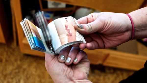 "Artist and flipbooked.com founder Liza Tudor thumbs through ""1st Steps,"" a flipbook of Nicole Garrens"