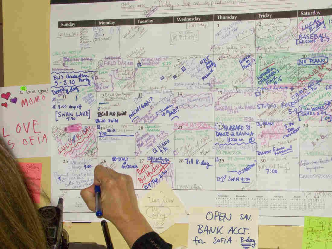 Woman writing on full calendar