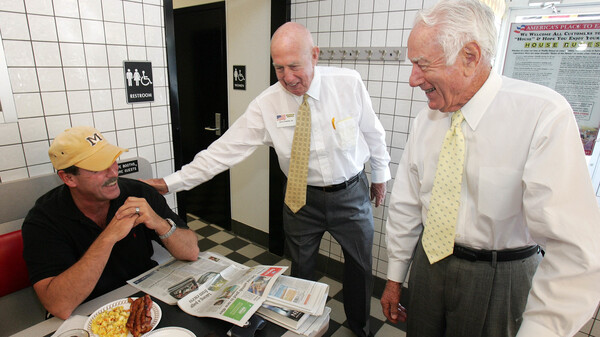 Waffle House founders Joe Rogers (center) and Tom Forkner (right) greet longtime customer John Webb as they stop for a meal at a Waffle House restaurant in Norcross, Ga., in 2005.