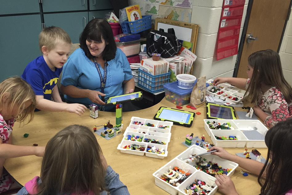 Anna Marie McClanahan (center) helps children write stories by using Legos to create scenes. (Pam Fessler/NPR)