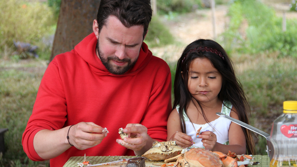 """Daniel Klein picks meat from crabs with the young daughter of a former strawberry picker in Oxnard, Calif., for an episode called """"A Day In The Life."""""""