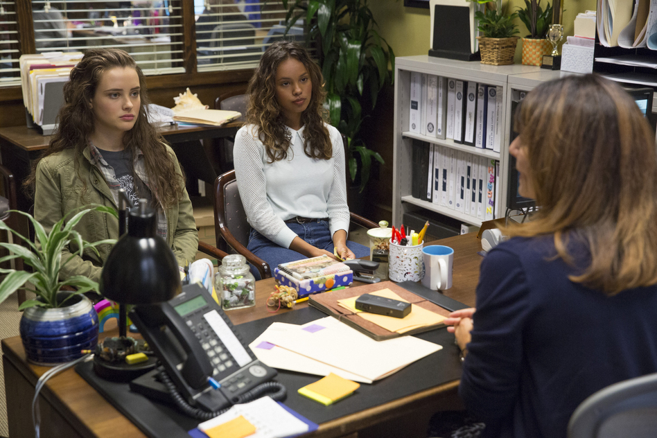 Actress Katherine Langford (left), who plays Hannah, a high school student who kills herself after enduring much bullying, and actress Alisha Boe (Jessica) sit in the counselor's office on <em>13 Reasons Why</em>. (Beth Dubber/Netflix)