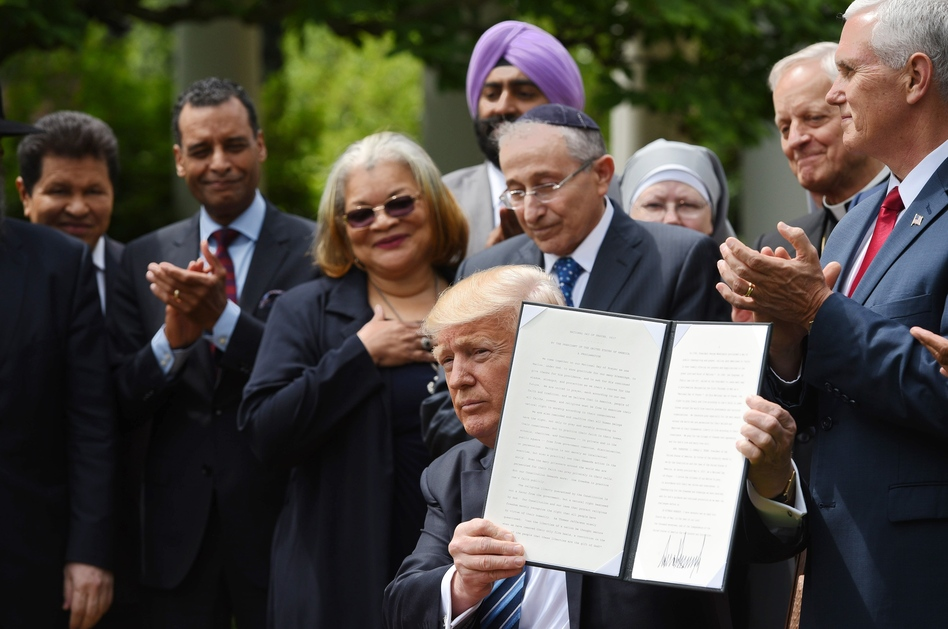 President Trump holds up a proclamation after signing it in the Rose Garden of the White House on Thursday. Trump said he was making it easier for churches and religious groups to take part in politics without risk of losing their tax-exempt status. (Mandel Ngan/AFP/Getty Images)
