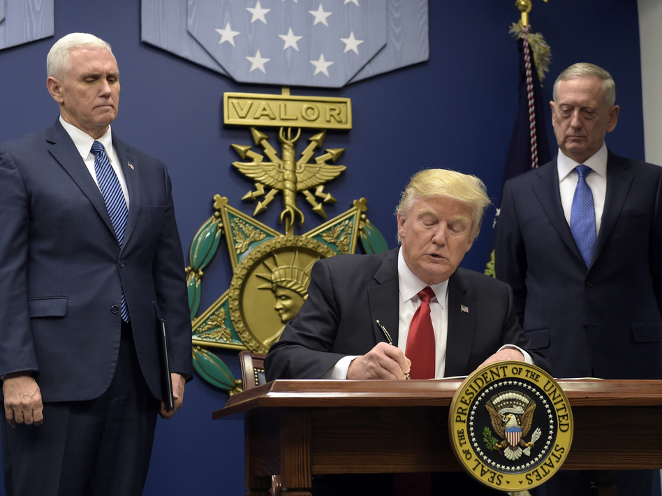 President Trump, with Vice President Pence (left) and Defense Secretary James Mattis (right) watching, signs an executive action on extreme vetting at the Pentagon on Jan. 27. (Susan Walsh/AP)