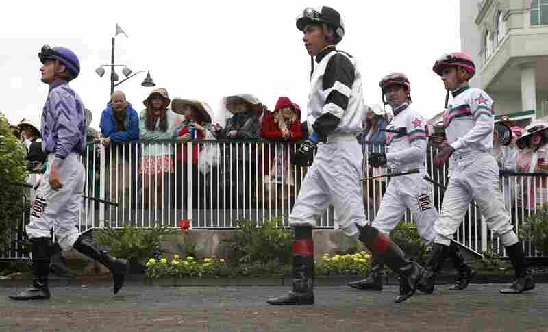 Jockeys walk through the paddock in a race before the 143rd running of the Kentucky Derby horse race at Churchill Downs Saturday.