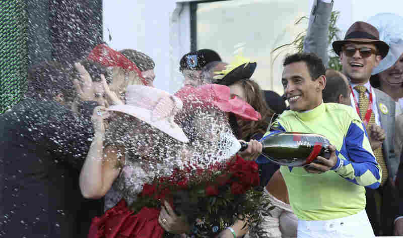 Jockey John Velazquez sprays the winning connections with champagne as he celebrates his victory aboard Always Dreaming in the 143rd running of The Kentucky Derby at Churchill Downs on Saturday.