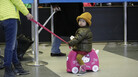 A girl waits as travelers walk though the security line at O'Hare International Airport.