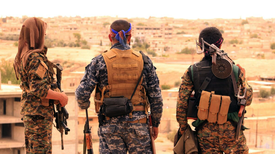 Members of the Syrian Democratic Forces look toward Tabqa, Syria. The U.S. announced Tuesday that it will begin arming Kurds allied with the SDF as the Pentagon prepares an offensive to retake the ISIS stronghold Raqqa. (Syrian Democratic Forces via AP)