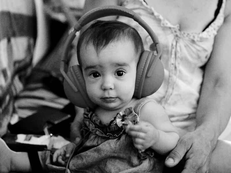 A baby wears headphones.