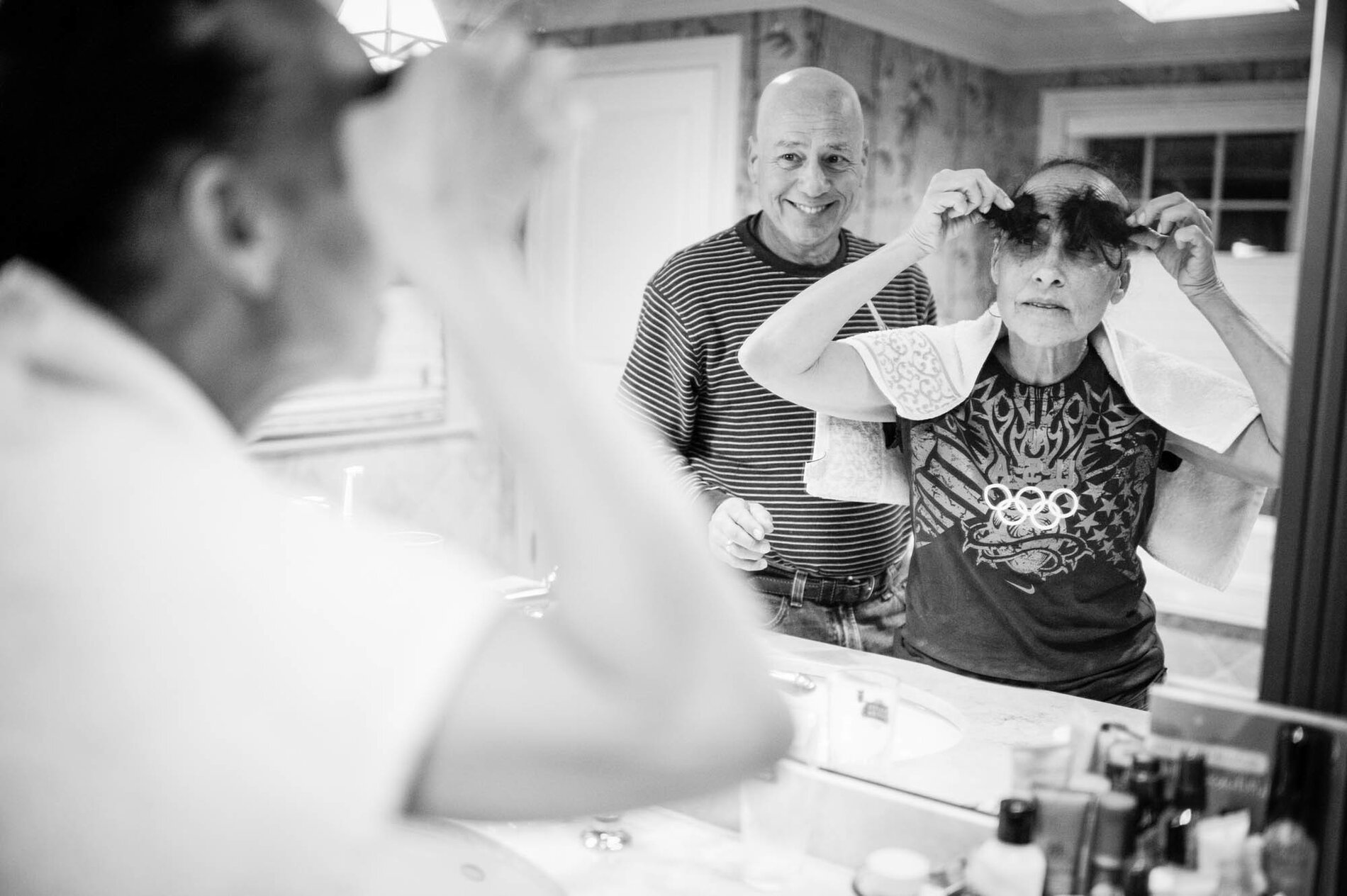 Late one evening, Dad cut Mom's hair, knowing that it would start falling out on its own in the coming weeks as a side effect from the chemotherapy. Mom turned the shorn locks into eyebrows.     (Nancy Borowick)