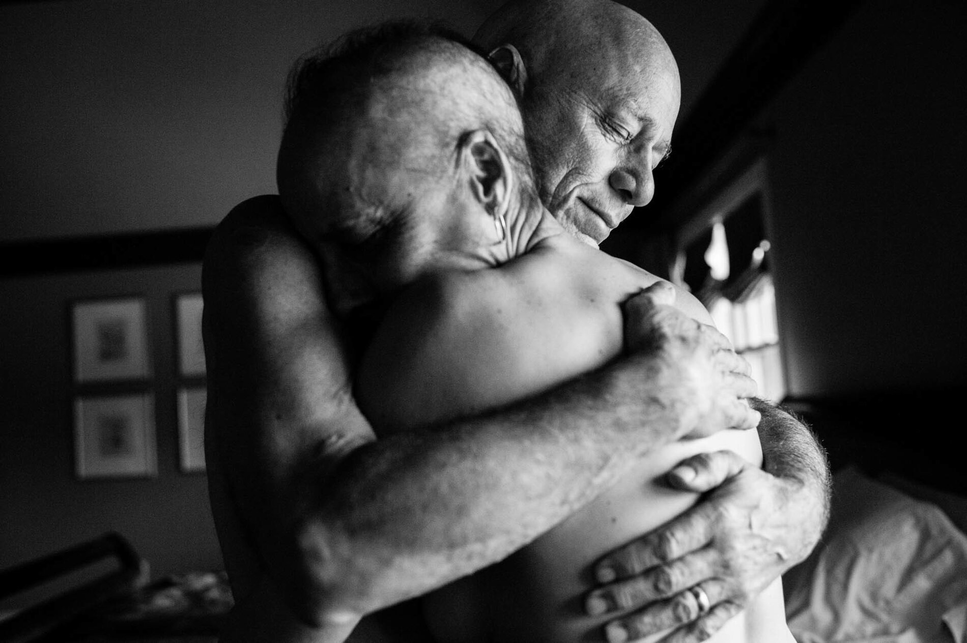 Dad and Mom embrace in the bedroom of their home. They never could have imagined both being in treatment for cancer at the same time. Together, they faced the daily struggles of illness in their own lives while also caring for each other.     (Nancy Borowick)