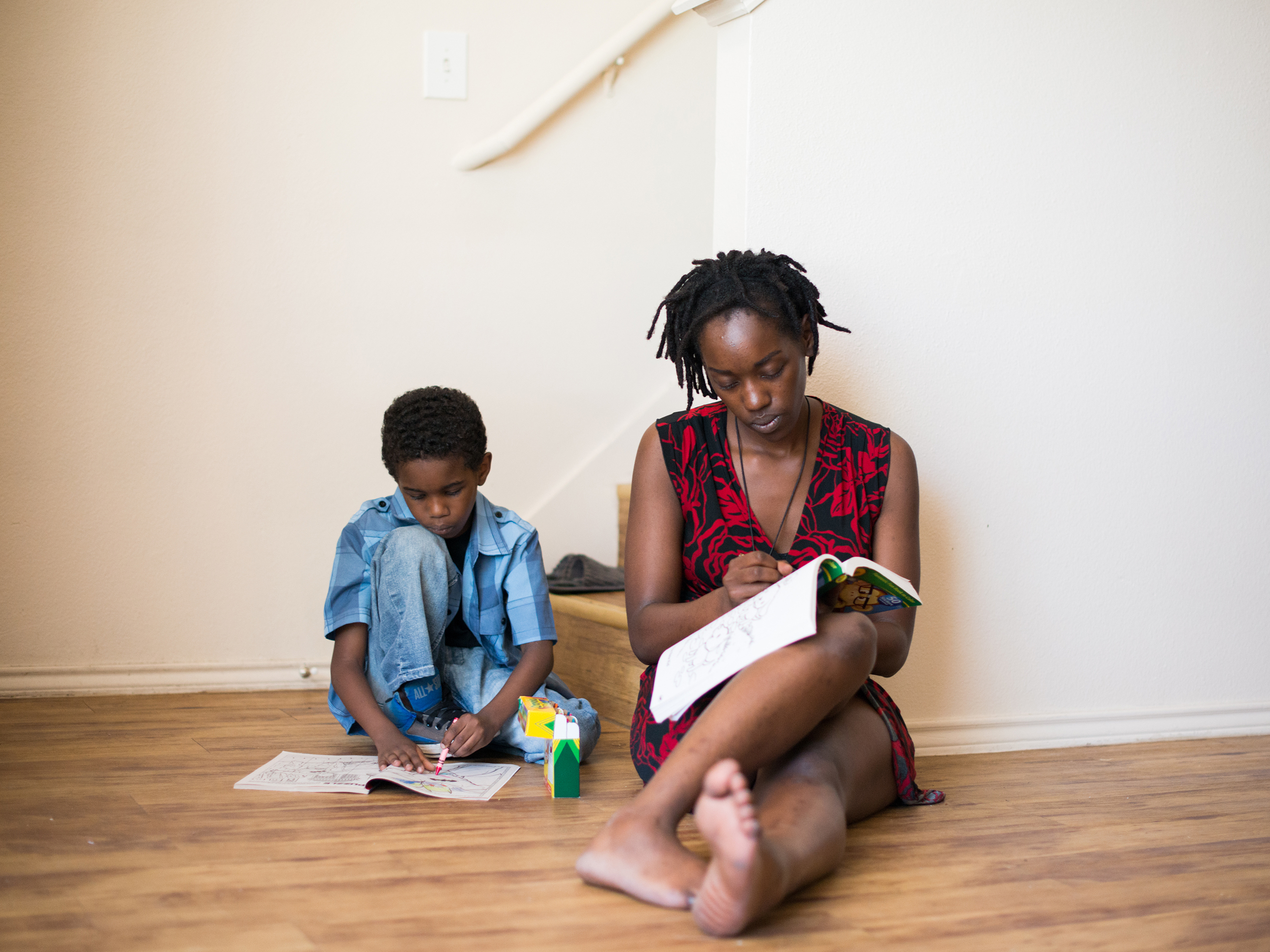Farryn Giles colors with her son Isaiah at their apartment in Dallas. (Brandon Thibodeaux for NPR)