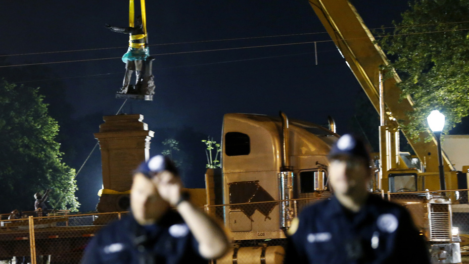 The statue of Jefferson Davis is removed from its base in New Orleans as police officers stand watch early Thursday. Demonstrators both for and against the removal of Confederate-era statues had gathered at the site. (Gerald Herbert/AP)