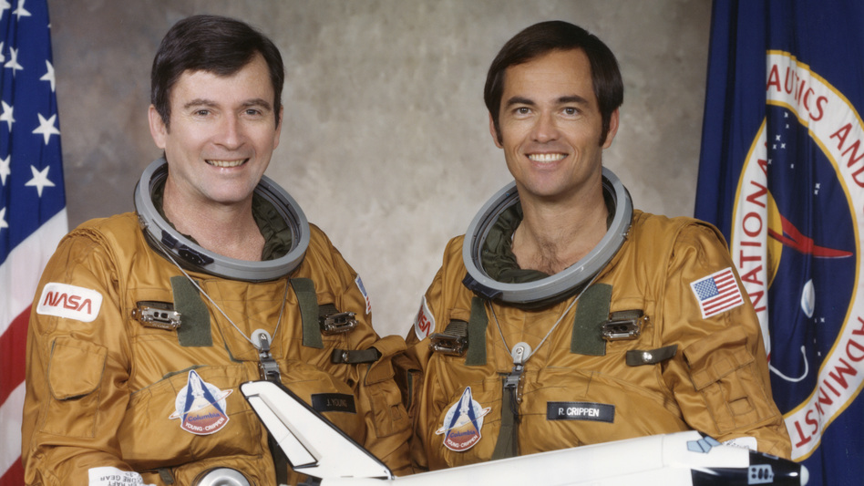 Astronauts John Young (left) and Bob Crippen, the crew of the first space shuttle mission, hold a model of the spacecraft. Young died Friday at age 87.