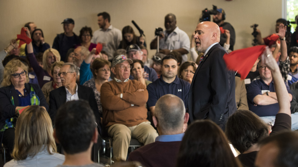 Audience members wave red flags in response to Rep. Tom MacArthur, R-N.J., at a raucous town hall Wednesday night in Willingboro. (Dominick Reuter/AFP/Getty Images)