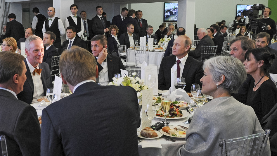 Michael Flynn (with his hand to his ear) sits next to Russian President Vladimir Putin at a dinner in Moscow on Dec. 10, 2015, celebrating the 10th anniversary of RT, an English-language TV channel funded by the Russian government.