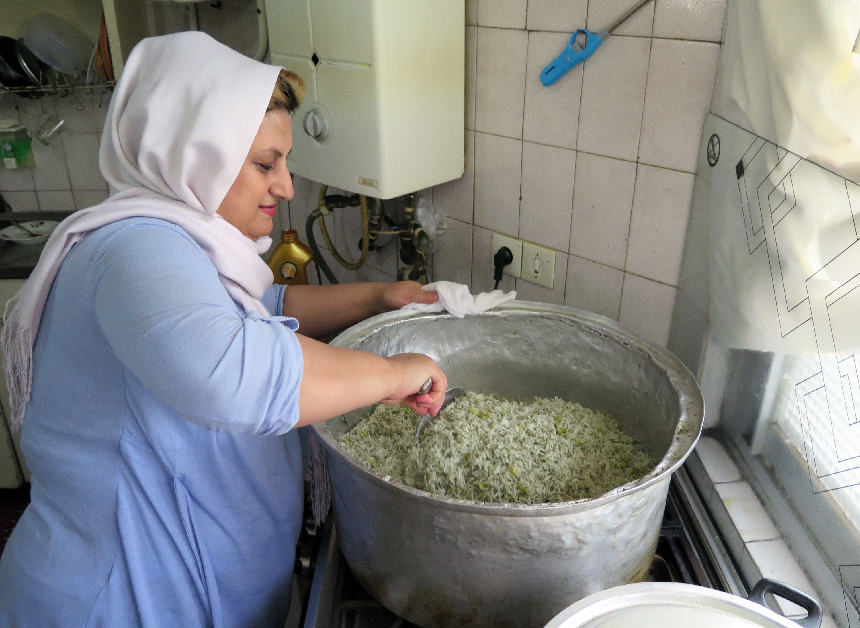 Maral Mohamedzadeh prepares food at her home for Mamanpaz, an organization that works with dozens of housewives to deliver home-cooked meals to businesses.     (Kevin Leahy/NPR)
