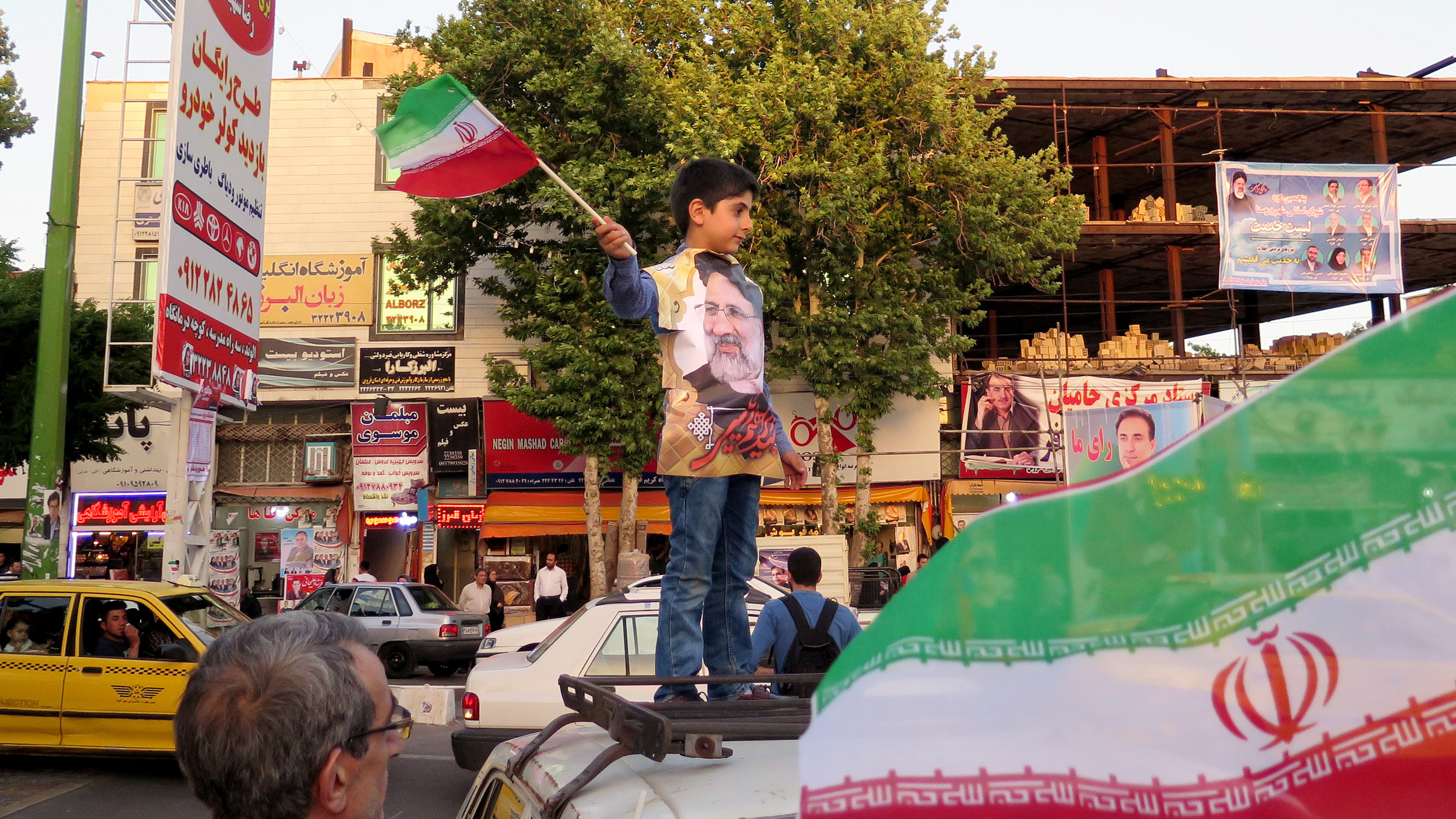A boy waves an Iranian flag at a rally in Qazvin on Wednesday for the conservative cleric Ebrahim Raisi, the presidential candidate pictured on the boy's shirt.     (Kevin Leahy/NPR)
