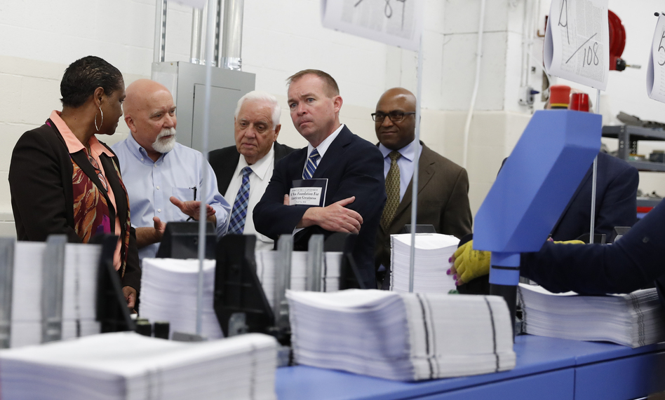 "White House Budget Director Mick Mulvaney (second from right) holds a copy of the president's 2018 budget at the Government Publishing Office's plant in Washington, D.C. Mulvaney describes the plan as ""taxpayer first."" (Carolyn Kaster/AP)"