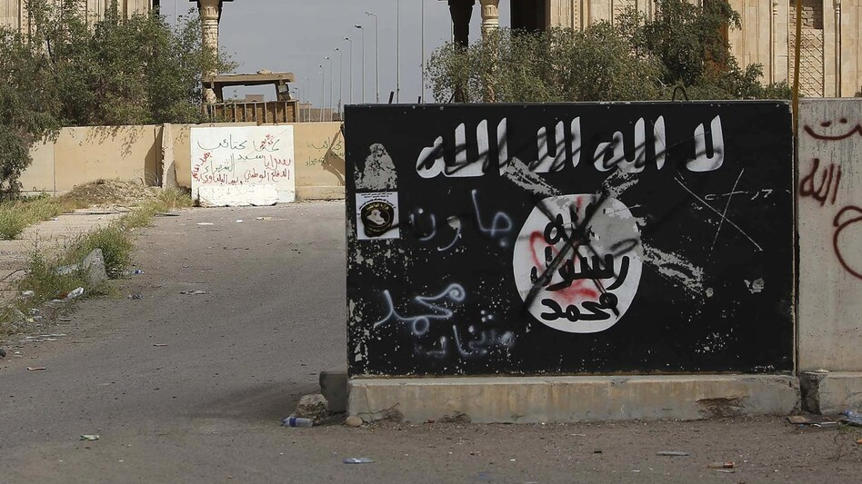 A defaced Islamic State flag is emblazoned on a wall in Tikrit, Iraq, in 2015. ISIS will generally claim responsibility for an attack within one day, though it can sometimes take longer. (Mohammed Sawaf/AFP/Getty Images)