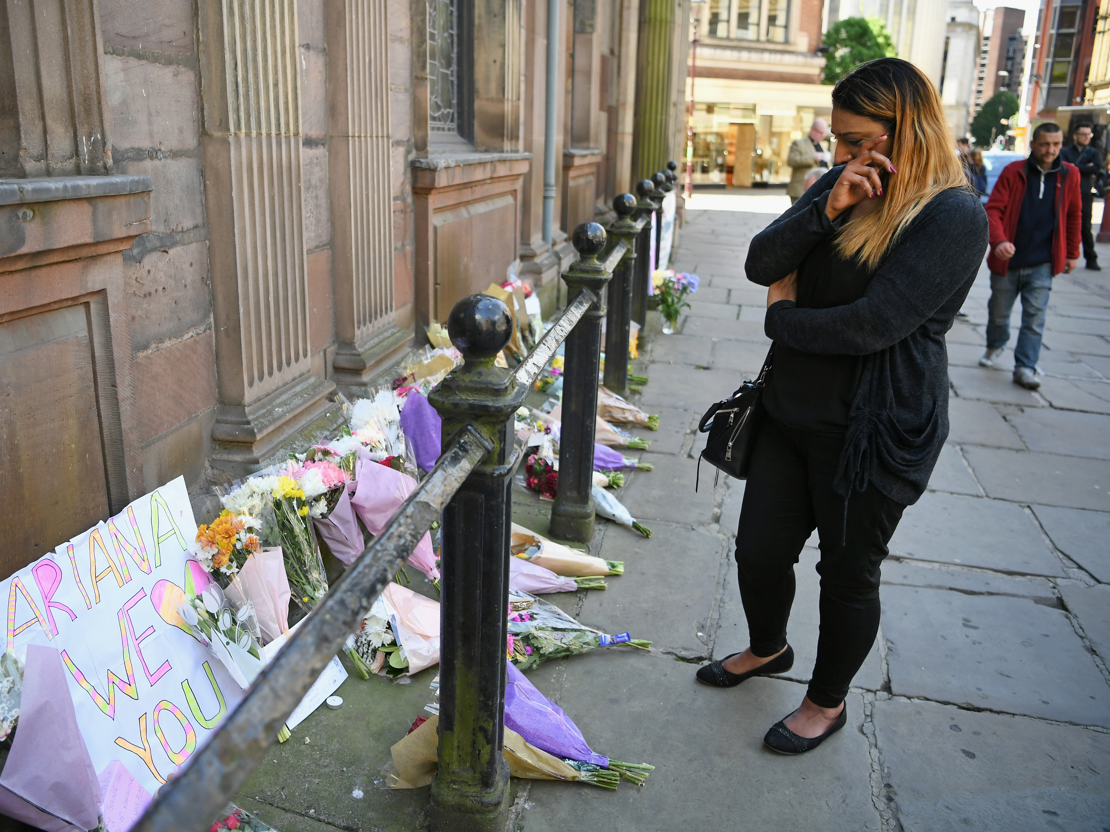 A woman looks at flowers left in Manchester's St. Ann Square on Tuesday, one day after a bomber carried out an attack at the end of an Ariana Grande concert in the city.     (Jeff Mitchell/Getty Images)