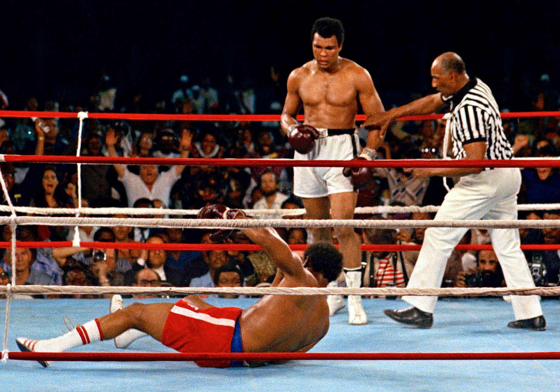 Muhammad Ali (center) watches after knocking down defending heavyweight champion George Foreman. (AP)