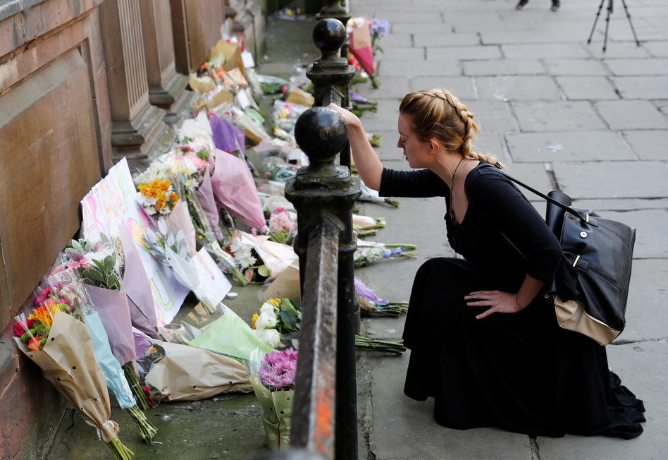 A woman lays flowers for the victims of the Manchester Arena attack in central Manchester, England, on Tuesday. (Darren Staples/Reuters)