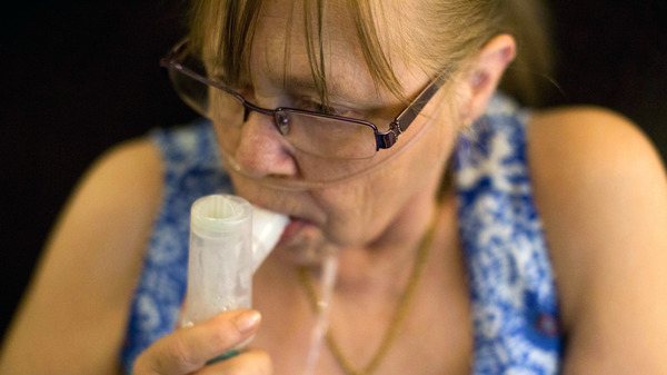 Juanita Milton, who suffers from COPD, uses her nebulizer with albuterol sulfate at her home in Live Oak, Texas.